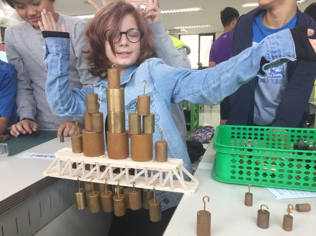 A student celebrates the success of her bridge design at Korea International School. (KIS)