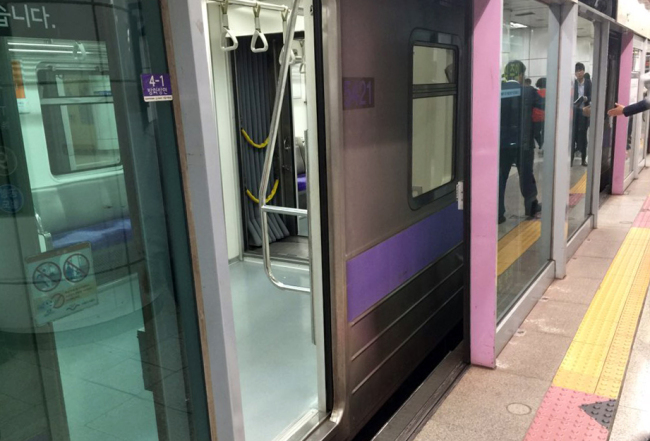 A subway train is seen at Gimpo International Airport Subway Station in Seoul with platform screen doors open. (Yonhap) & Commuter killed trapped between subway door and train