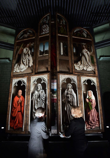 """This file photo taken on Oct. 12 shows officials unveiling the restored exterior panels of """"The Adoration of the Mystic Lamb,"""" an altar piece painted by the Van Eyck brothers in 1432, at Saint Bavo Cathedral in Ghent, Belgium. (Emmanuel Dunand/AFP-Yonhap)"""
