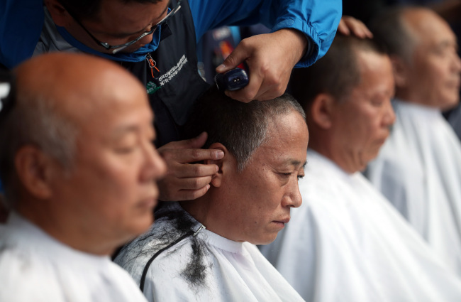 Activists shave their heads in protest against the authorities' move to impose an autopsy on the body of Baek Nam-gi against his family's wishes. Baek, an activist farmer, died on Sept. 25, about 10 months after being knocked down by a blast from a police water cannon during a rally. (Yonhap)