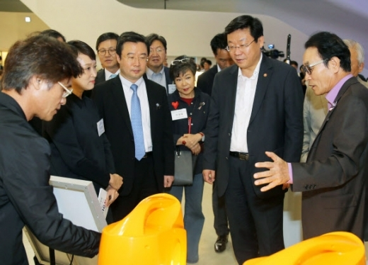 Joo Hyung-hwan (second from right), Korea's Minister of Trade, Industry and Energy, looks at prototypes of design products at a design-related event held at Dongdaemun Design Plaza in August. (Yonhap)