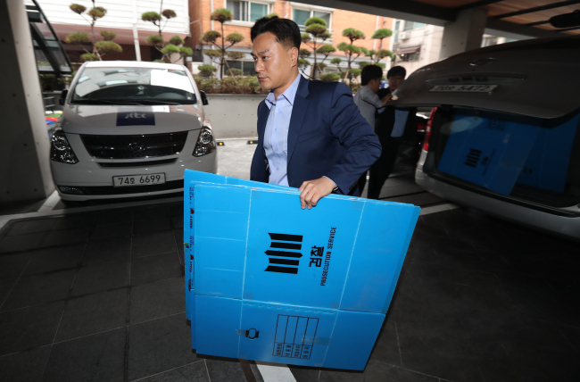 An investigator takes paper boxes into the K-Sports Foundation building in Gangnam, southern Seoul, Wednesday, as the prosecution begins a search of the foundation's office as part of an ongoing investigation. (Yonhap)