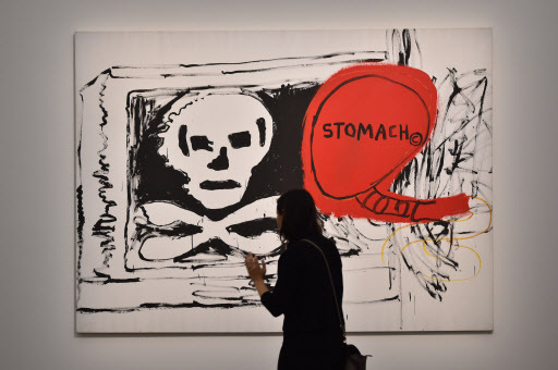 """A woman visits the exhibition """"Jean-Michel Basquiat,"""" a retrospective on Jean-Michel Basquiat's career from graffiti in New York to more complex work, at the Mudec Museum in Milan on Thursday. (AFP-Yonhap)"""