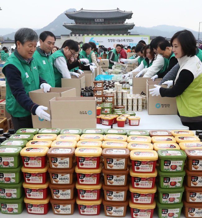 Daesang Corp. CEO Myung Hyung-sup (left), employees and volunteers put together 6,000 presents, composed of Daesang Chungjungone's signature red pepper paste and other groceries, for donation as part of the firm's 60th founding anniversary event at Gwanghwamun Plaza, central Seoul, Monday. (Yonhap)