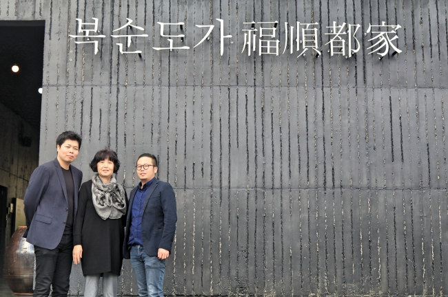 Family owners of Boksoondoga rice wine winery Kim Min-kyu, Park Bok-soon and Kim Min-kook pose in front of the brewery headquarters in Ulsan. (Julie Jackson/The Korea Herald)