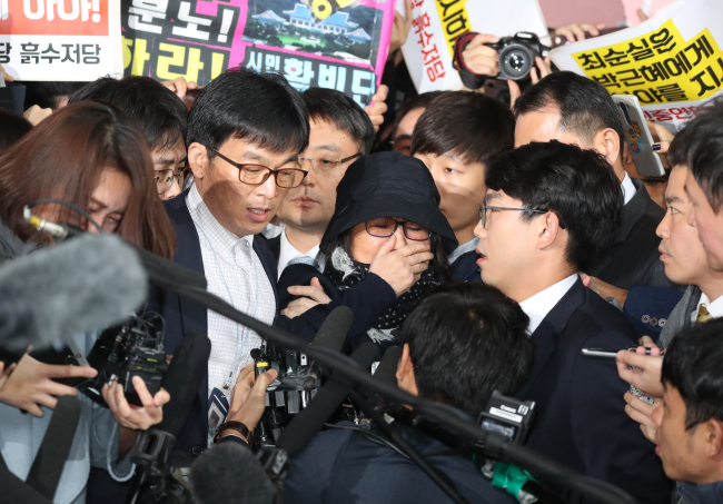 Choi Soon-sil enters the Seoul Central District Court for questioning, with her glasses and hat removed, amid a horde of reporters Monday. (Yonhap)