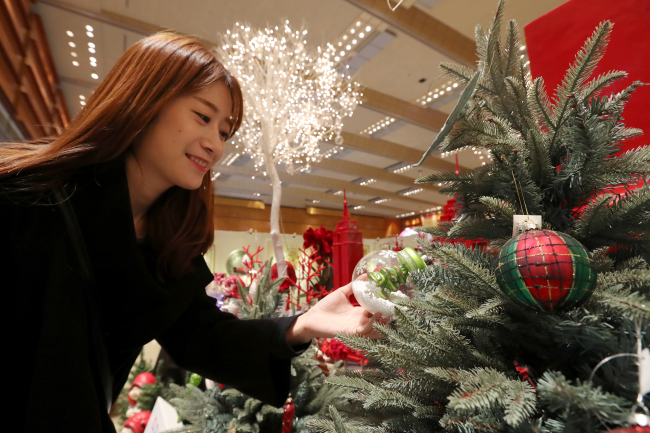 A visitor looks at a Christmas tree and ornaments displayed at the event Food Week Korea 2015, held at Coex, Samseong-dong, Seoul, Wednesday. (Yonhap)