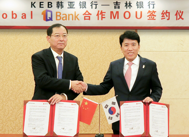 KEB Hana Bank CEO Ham Young-joo (right) shakes hands with Gao Zhuang, president of the Yanbian branch of the Bank of Jilin, Wednesday, after signing a memorandum of understanding to share KEB Hana's fintech knowledge. (KEB Hana Bank)