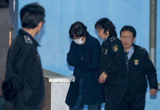Choi Soon-sil (center) enters a court room to attend a hearing on the court's review on the arrest warrant for her on Thursday. (Yonhap)