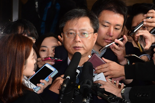 Woo Byung-woo, former chief legal adviser to President Park Geun-hye, arrives at the Seoul Central Prosecutors' Office on Sunday. (Yonhap)