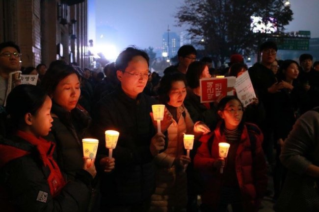 Family members hold candles during the anti-Park Geun-hye rally held at Gwanghwamun Square, central Seoul, Saturday. (Son Ji-hyoung/The Korea Herald)