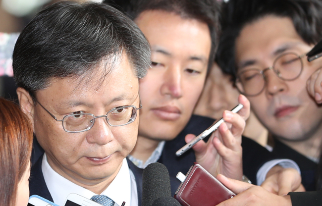 Woo Byung-woo, former senior presidential secretary for civil affairs, looks at reporters when asked about his embezzlement charges, before entering the Seoul Central District Prosecutors' Office for questioning on Sunday. (Yonhap)