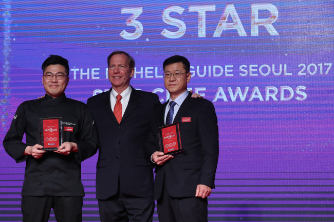 International director of the Michelin Guides Michael Ellis (center) poses with Korea's Michelin three-star chefs, Lee Byeong-jin of Gaon (left) and Kim Sung-il of La Yeon, at the Michelin Guide Seoul launch event held at The Shilla Seoul on Monday. (Yonhap)