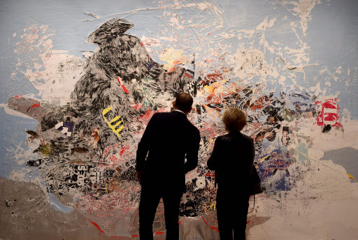 """People look at Mark Bradford's """"Let's Make Christmas Mean Something This Year"""" on display during the media preview on Friday for Sotheby's New York evening auctions of impressionist, modern and contemporary art in New York. (AFP-Yonhap)"""