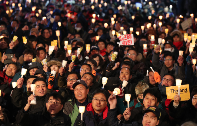"Protesters hold candles at a rally demanding for the resignation of President Park Geun-hye near Cheonggye Stream in central Seoul on Wednesday. Signs in front of the crowd read, ""Park Geun-hye out."" (Yonhap)"