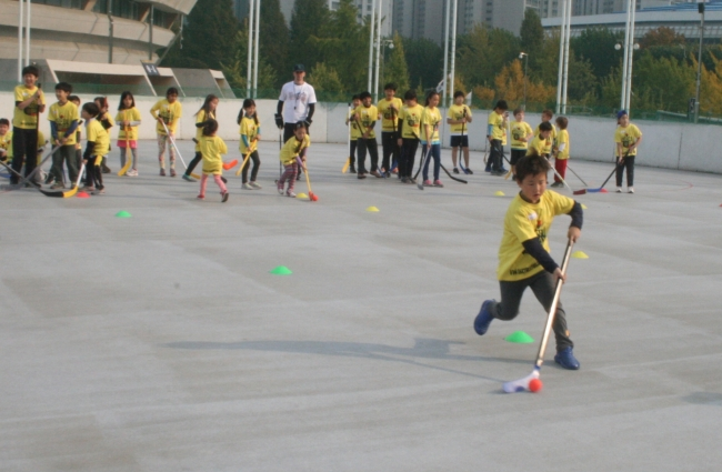 Children take part in a ball hockey relay activity at the Hockey Day event at Jamsil Sports Complex on Saturday. (Paul Kerry/The Korea Herald)