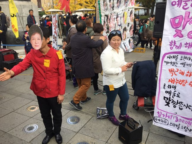 A woman dressed as Choi Soon-sil pose for picture at the rally scene in Gwanghwamun Square, central Seoul on Saturday. (Ock Hyun-ju/The Korea Herald)
