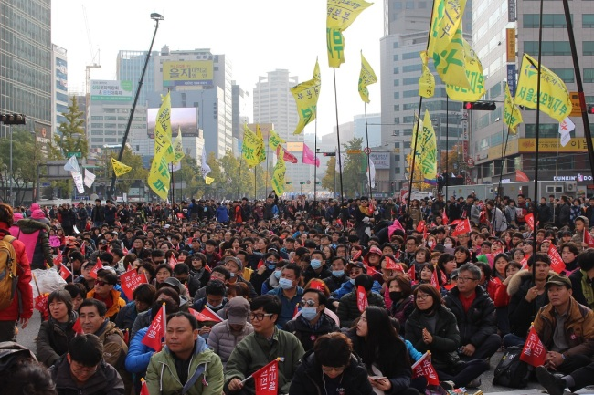 Some thousands of protestors hold up signs demanding for President Park Geun-hye's resignation in Seoul Square in front of Seoul's Cityhall on Saturday. (Jo He-rim/The Korea Herald)