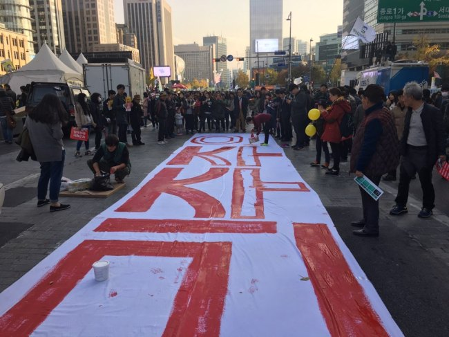 Protestors color in a poster reading,