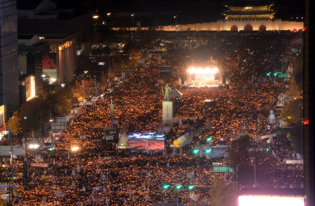 Tens of thousands of rally-goers hold candles in Gwanghwamun Square, central Seoul on Saturday. (Yonhap)