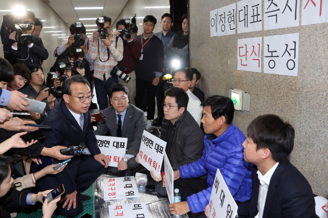 Saenuri Party Chairman Rep. Lee Jung-hyun meets party officials who are on a hunger strike demanding his resignation from the party leadership in front of the lawmaker's office at the National Assembly in Seoul on Monday. (Yonhap)