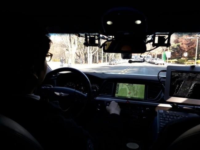 SNU students sit behind the wheel of self-driving car Snuber 2. (Shin Ji-hye / The Korea Herald)