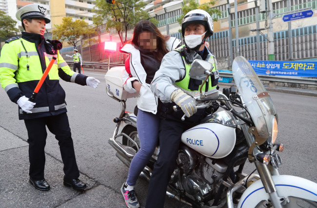 A test-taker arrives on police patrol bike. (Yonhap)
