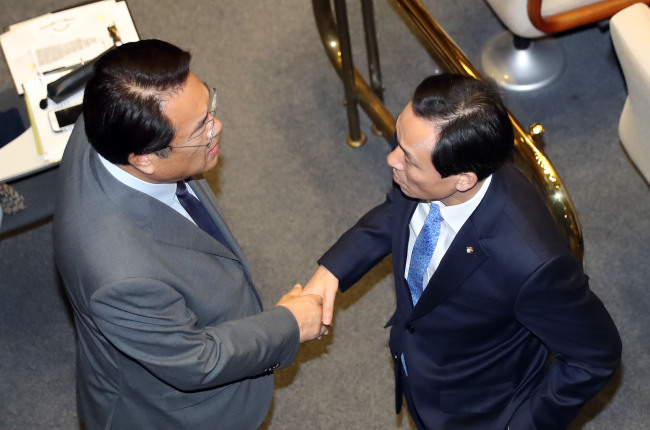 Saenuri floor leader Rep. Chung Jin-suk (left) shakes hands with his opposition counterpart Woo Sang-ho during a plenary session at the National Assembly on Thursday. (Yonhap)