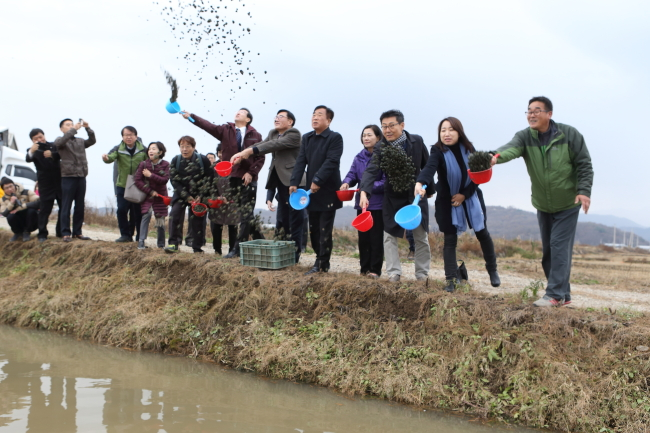 Residents and officials throw food for migratory birds at a field, as part of a program hosted at the DMZ Peace Town for Migratory Birds in Cheorwon, Gangwon Province. (Cheorwon County)