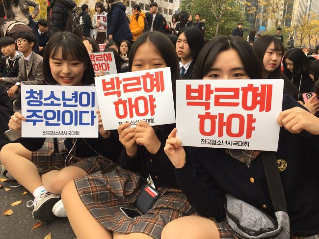 "Three students hold signs reading ""Expel Park Geun-hye"" at a rally in front of Bosingak Bell, central Seoul on Saturday. (Jo He-rim/The Korea Herald)"