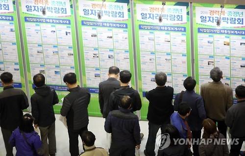 Job seekers check out job advertisements displayed at a job fair. Yonhap