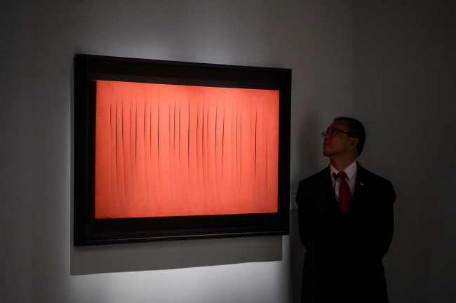 """A security member looks at Lucio Fontana's 'Concetto Spaziale, Attese at """"The Loaded Brush"""" display by auction house Christie's in Hong Kong on Nov. 23, 2016. (Yonhap-AFP)"""