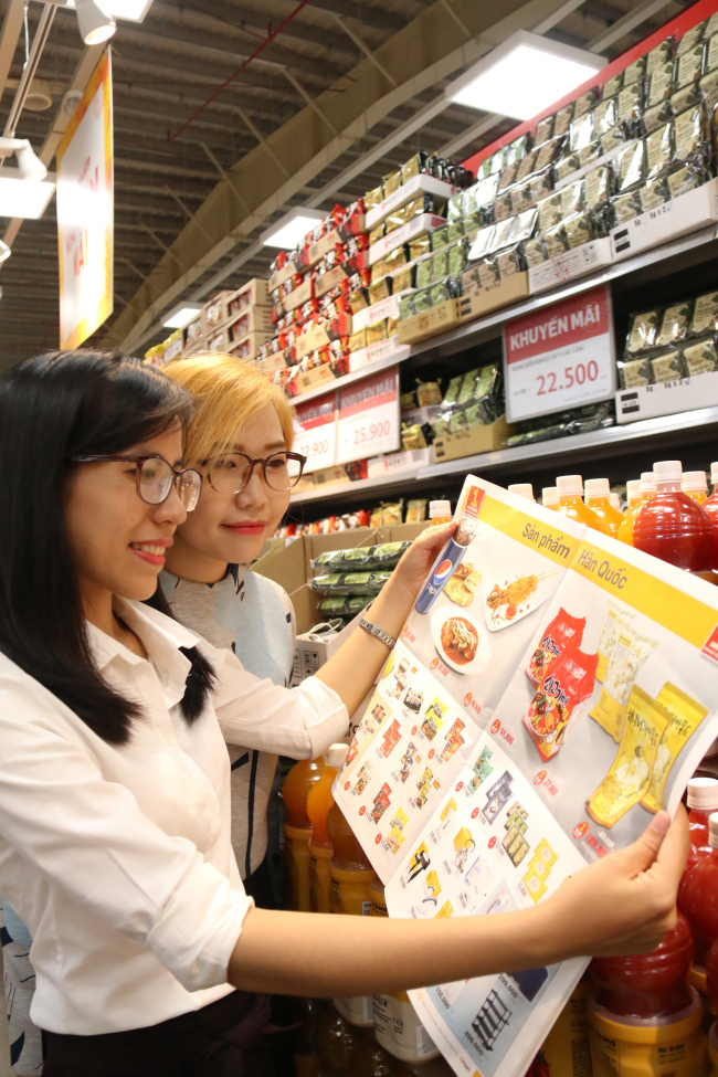 Shoppers in Ho Chi Minh look closely at a brochure listing an array of discounted Korean products at the E-mart Go Vap branch. The first E-mart store in Vietnam announced Sunday it would kick off a discount event in collaboration with state-run trade promotion agency KOTRA by Dec 7. Yonhap