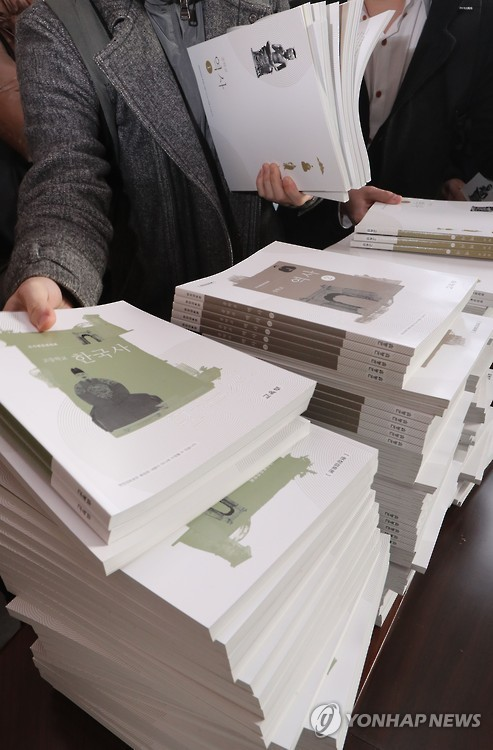 An education ministry official distributes the pilot editions of controversial state-authored history textbooks to journalists at the government complex in Seoul on Nov. 28, 2016. (Yonhap)