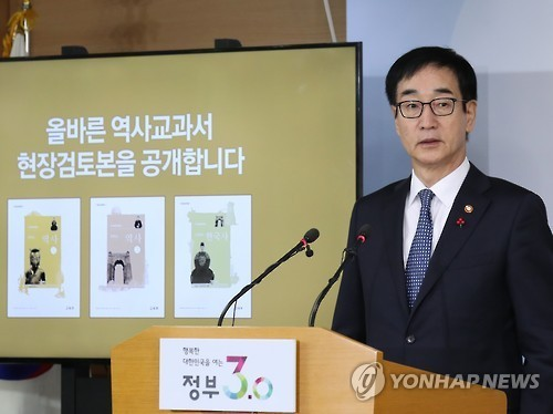 Lee Joon-sik, education minister and deputy prime minister for social affairs, formally unveils the three draft versions of controversial state-authored history textbooks at the government complex in Seoul on Nov. 28, 2016.(Yonhap)