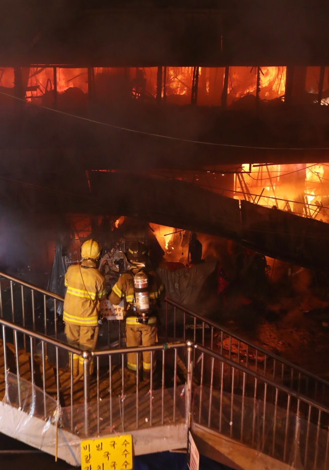 Firefighters extinguish a blaze in Seomun Market in Daegu early Wednesday. Some 800 stores were completely gutted, but no casualities were reported (Yonhap)