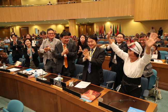 """A Korean delegation cheers as female divers of Jeju Island, or """"haenyeo,"""" are added to the UNESCO intangible cultural heritage list during the UN body's meeting in Addis Ababa, Ethiopia, Thursday. (Cultural Heritage Administration)"""