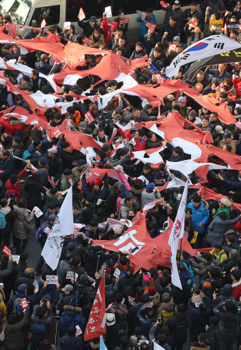 Protestors tear apart the flag of Saenuri Party in front of its head office on Saturday. (Yonhap)