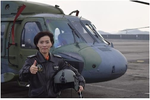 Army warrant officer Jung Eun-hee poses in front of a UH-60 helicopter in this photo provided by South Korea's military. (Yonhap)