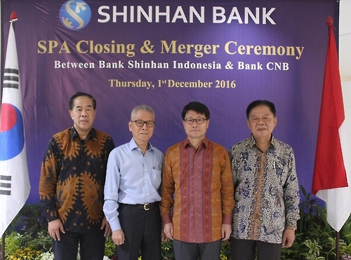 Suh Tae-won (2nd from R), head of Shinhan Bank Indonesia, poses for a photo in a ceremony at the headquarters of Centratama Nasional Bank on Dec. 1, 2016. The photo was provided by Shinhan Bank. (Yonhap)
