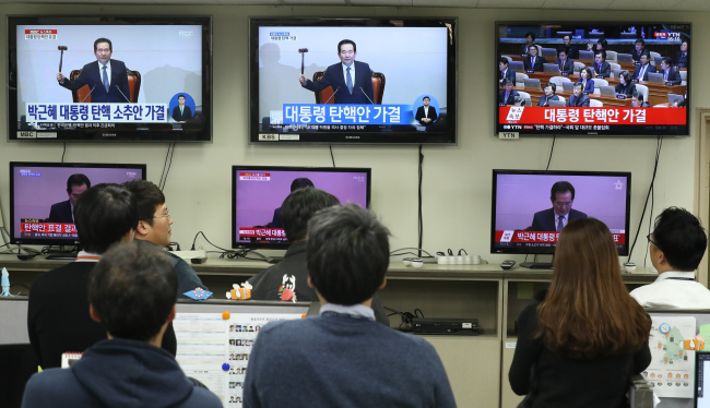 Civil servants in Seoul watch the live news as the parliament declares the passage of the impeachment bill. (Yonhap)