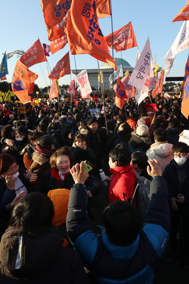 Citizens gathered in front of the National Assembly on Friday cheer after hearing that the motion for President Park Geun-hye's impeachment has been passed. (Yonhap)