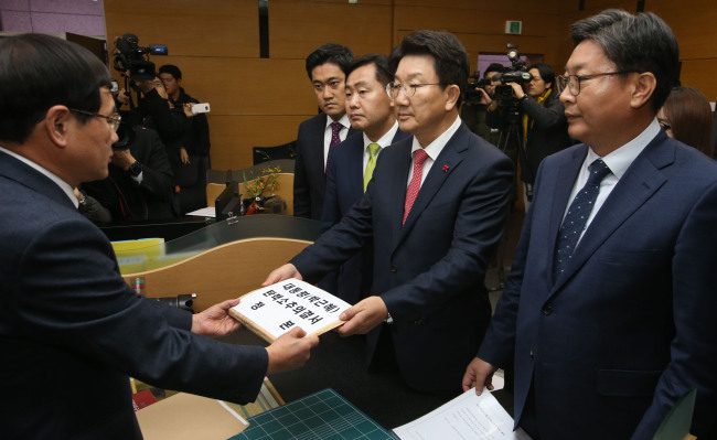 Rep. Kweon Seong-dong, a chairman of Legislation and Judiciary Committee, hands in the impeachment document to the civil affairs department at the Constitutional Court in Seoul on Friday. (Yonhap)