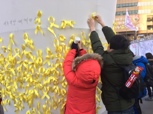 Citizens stick yellow ribbons to a wall in Gwanghwamun Square, Seoul, Saturday to pay respect to the victims of the 2014 Sewol ferry disaster. (Ock Hyun-ju/The Korea Herald)