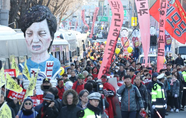 Protestors march towards the presidential office during the seventh rally against President Park Geun-hye held in central Seoul, Saturday. (Yonhap)