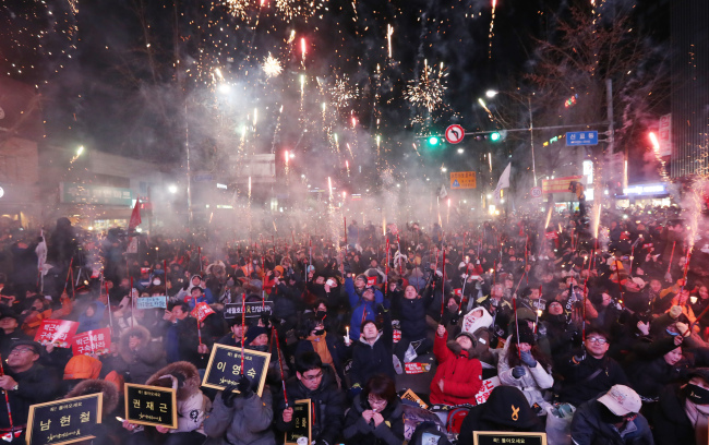 Fireworks are displayed to celebrate the impeachment of President Park Geun-hye during the seventh rally against President Park Geun-hye in central Seoul, Saturday. (Yonhap)