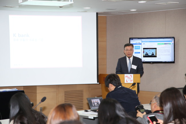 K-Bank CEO Shim Sung-hoon delivers a presentation about the new bank at the Seoul government complex in Gwanghwamun on Wednesday.