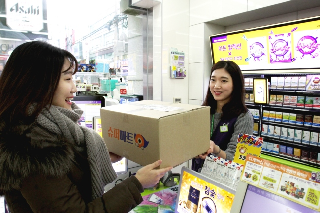 A user of Ticket Monster's mobile shopping app TMon picks up her delivered product at a CU convenience store in a file photo. (Ticket Monster)