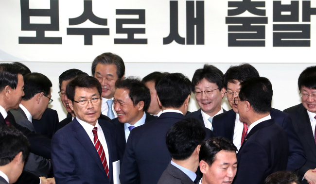 "The lawmakers defecting from the ruling Saenuri Party on Tuesday pledge to create a new conservative party. Behind them is a banner reading ""starting anew as conservatives."" (Yonhap)"