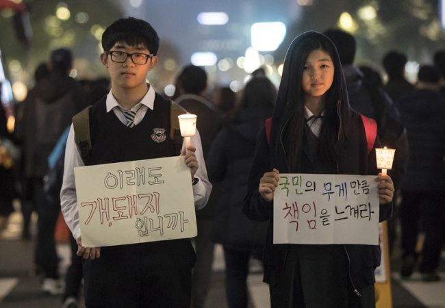 Two high school students hold banners and candles during the fourth Saturday rally against President Park Geun-hye in central Seoul on Nov.19. (Yonhap)